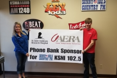 Lisa and Cole Lester hold up Aera's sponsorshop sign for the St. Jude's Children's Hospital Radiothon.