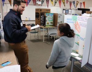 Aera's Alphonso Valencia interviews a Grimmway Academy student about her science-fair project.