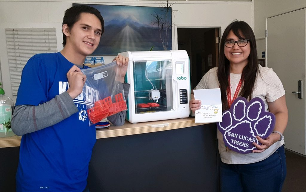 San Lucas School's Jessica Riley (right) and her son Josh with the orange filters produced by the 3-D printer. More filters are shown being created inside the printer. Jessica holds a card from students thanking healthcare workers for their efforts. The cards are given to groups that receive the masks.