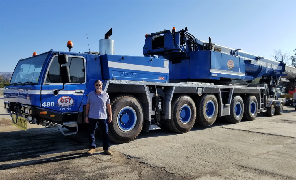 OST President Dennis Zermeno poses with his brand-new 250-ton crane that's just arrived in the company's Ventura yard.