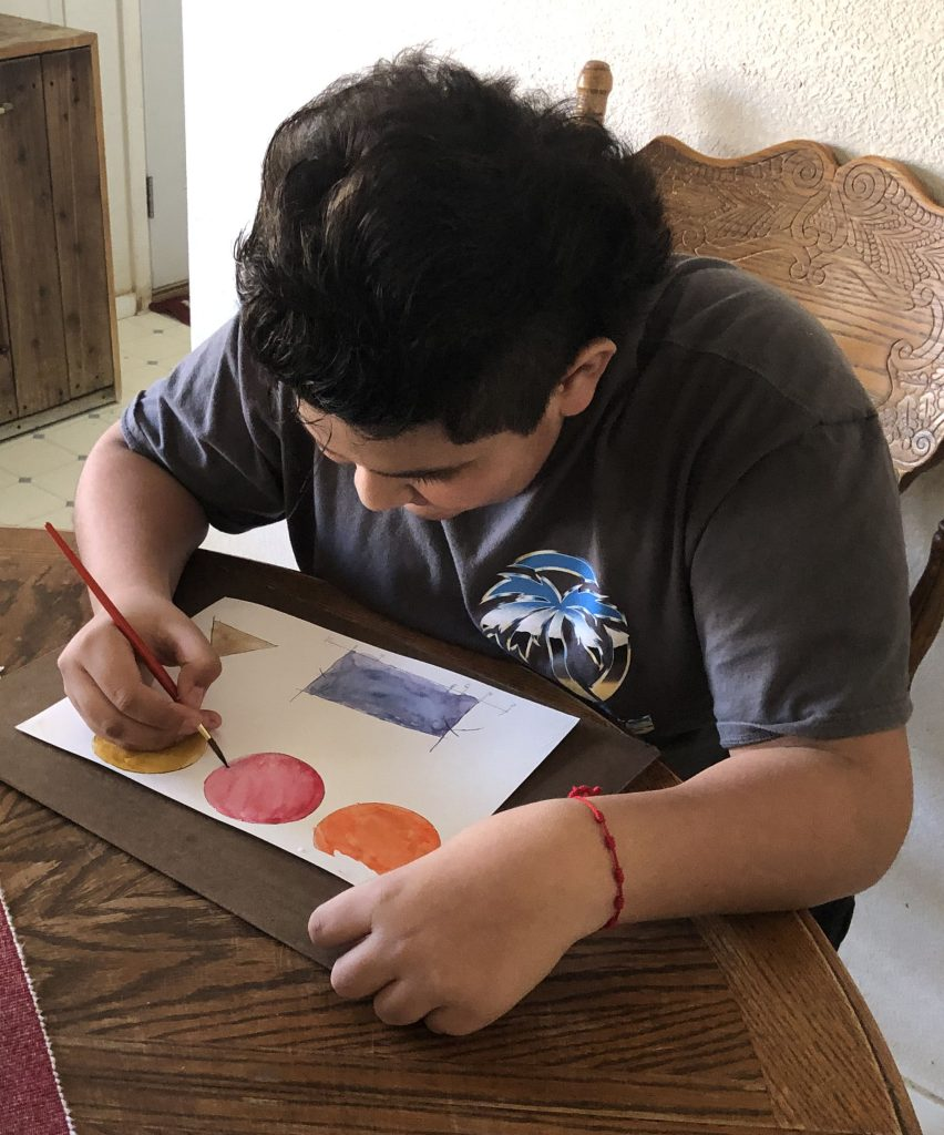 Ramon, a student at San Lucas School, uses his watercolor supplies to add dimension to his shapes as part of a Watercolor for Math Engagement assignment.