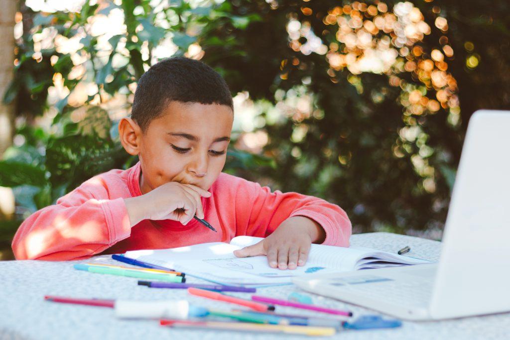 Boy doing homework outdoors