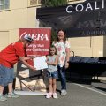 Aera volunteers Therese Santos (left) and Donna King (right) give a binder to Kamryn Nelson (center) at the city of Coalinga's 2021 National Night Out event. Volunteers gave out 200 binders to students from Coalinga schools.