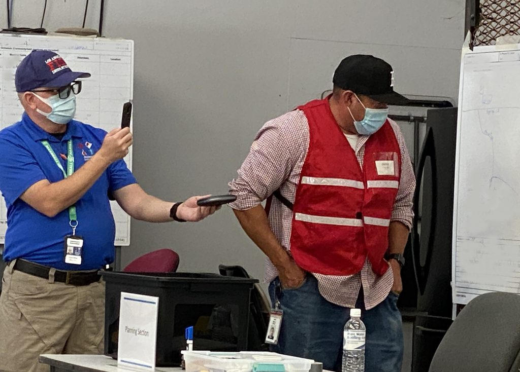 Chris Miller (left), an Aera emergency response specialist, holds up two phones for a video call as Albert Madrid (right), a San Ardo subsurface specialist, reviews response plans with representatives from California Department of Fish and Wildlife's Office of Spill Prevention and Response, who took part in the drill remotely.