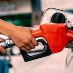 Hand holding gas nozzle in gas station for car refueling